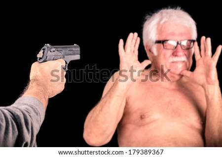 Criminal threatening scared old man with a Gun - stock photo