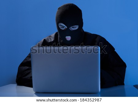 Criminal using laptop to hack online account at table - stock photo