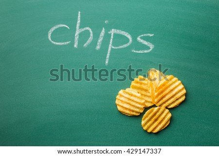 Crinkle cut potato chips on green chalkboard. Tasty spicy potato chips. - stock photo