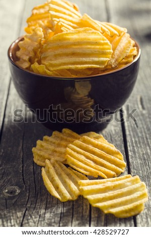 Crinkle cut potato chips on kitchen table. Tasty spicy potato chips in bowl. - stock photo