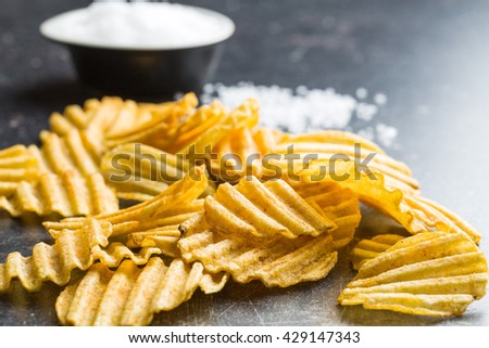 Crinkle cut potato chips on kitchen table. Tasty spicy potato chips with salt. - stock photo
