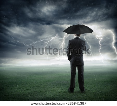 crisis - businessman below storm with umbrella  - stock photo
