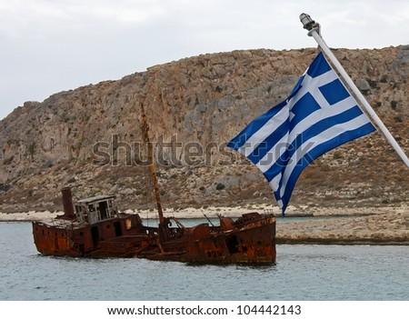 Crisis in Greece. Greek flag sailing over sank rusty ship - stock photo