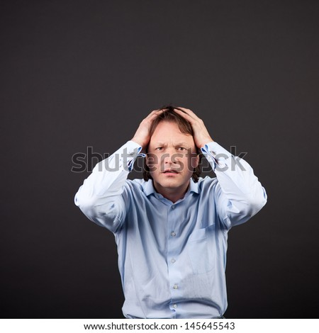 Crisis in the job as a young businessman reacts by holding his hands to his head with a look of desperation on a dark background - stock photo