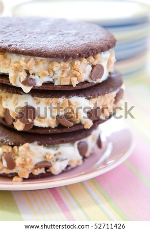 Crisp cookies sandwich creamy vanilla ice cream mixed with milk chocolate chips and toffee chunks - stock photo