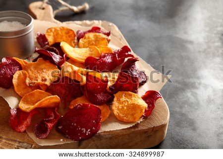 Crisp crunchy organic vegetable chips with fried or oven-baked potato and beetroot chips served as a finger food snack on a wooden chopping board with sea salt and copyspace - stock photo