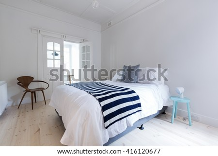Crisp white Danish stylish bedroom with striped throw rug and blue side table - stock photo