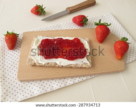 Crispbread with cream cheese and strawberry jam - stock photo