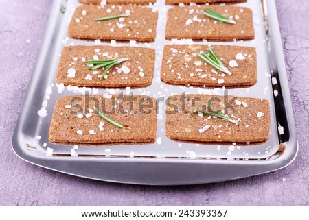 Crispbread with salt and sprigs of rosemary on metal tray and color wooden background - stock photo