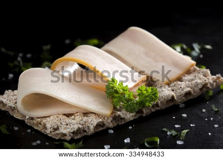 Crispbread with smoked turkey fillet and parsley over dark background - stock photo