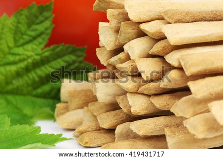 Crispy crunchy wheat bread sticks closeup on a background of tomato and green leaf. - stock photo