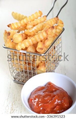 Crispy French Fries in a wire fryer basket with a spicy red pepper aoli - stock photo