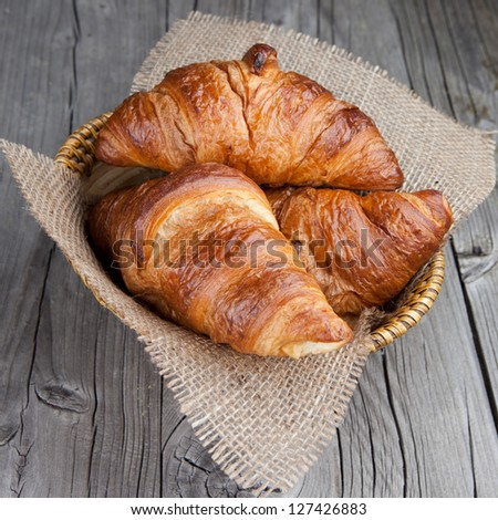 Crispy fresh croissants in a basket on a wooden table - stock photo