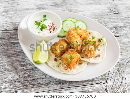 Crispy fried fish on a homemade tortilla on a light  rustic wooden background - stock photo