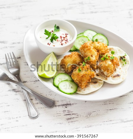 Crispy fried fish on a homemade tortilla on a light wooden background - stock photo