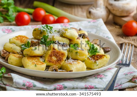 Crispy fried gnocchi with mushrooms, herbs and parmesan - stock photo