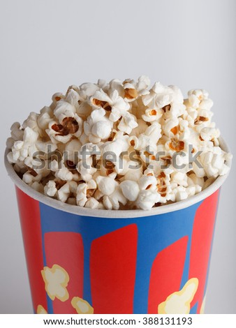 crispy fried popcorn in striped box on a gray background close-up - stock photo