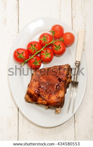crispy marinated ribs with meat fork and fresh tomatoes on an oval plate - stock photo