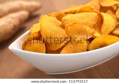 Crispy Peruvian sweet potato chips in white ceramic bowl with sweet potatoes in the back (Selective Focus, Focus one third into the sweet potato chips) - stock photo