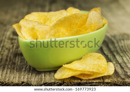 Crispy potato chips in green bowl on wooden boards - stock photo