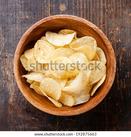 Crispy potato chips on wooden background - stock photo
