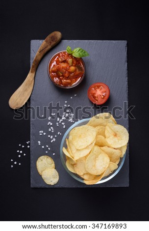 Crispy potato chips with sea salt in glass bowl, tomato sauce, basil and wooden spatula over stone board, black background. Top view. - stock photo