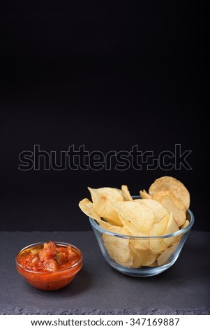Crispy potato chips with sea salt in glass bowl, tomato sauce, on stone board, black background, copy space. - stock photo