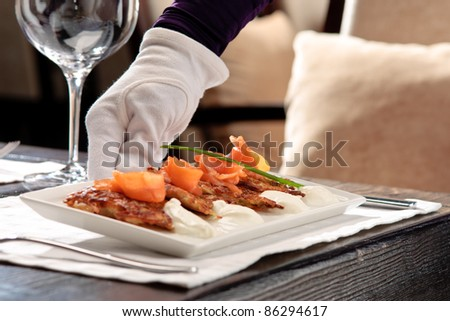 Crispy potato pancakes decorated with salmon and sour cream being served by a waiter - stock photo