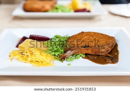 Crispy roasted honey glazed pork chop with vegetables, sweet potato fries, and marsala portobello mushroom sauce. - stock photo
