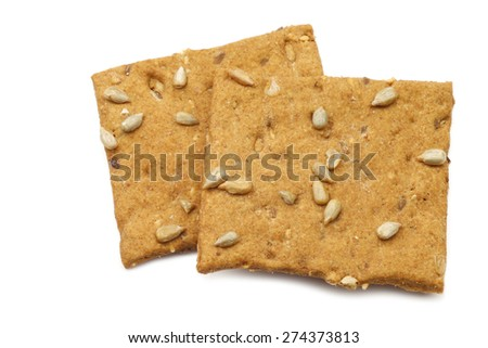 crispy spelt crackers with sunflower seeds on a white background - stock photo
