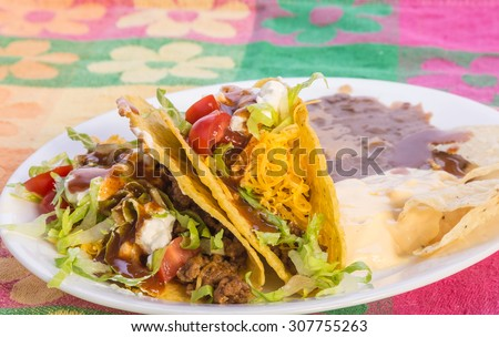 Crispy tacos on platter with refried beans and chili con queso on vivid colors of Mexican Restaurant Place Mat. - stock photo