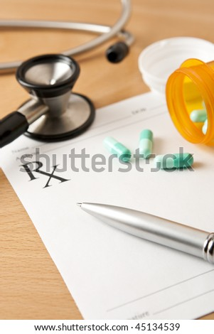 Critical focus on tip of pen. Stethoscope and bottle cap beyond depth of field. - stock photo