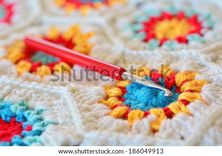 Crochet hook needle on granny square blanket. Concept photo of handmade art and crafts - stock photo