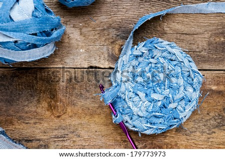 Crochet needles with hook on old wooden background. Recycling of old jeans - stock photo