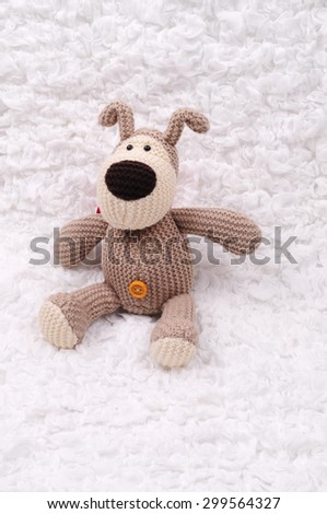 Crocheted bear sitting on the white cloth - stock photo