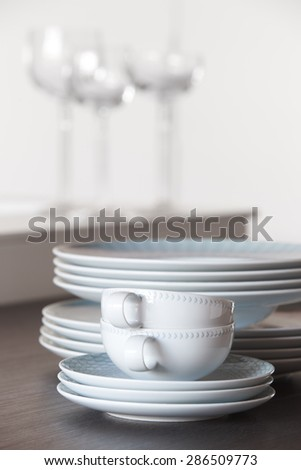 Crockery set over a table and cups with white background. Vertical - stock photo