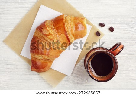 Croissant and cup of hot coffee on rustic table, top view - stock photo