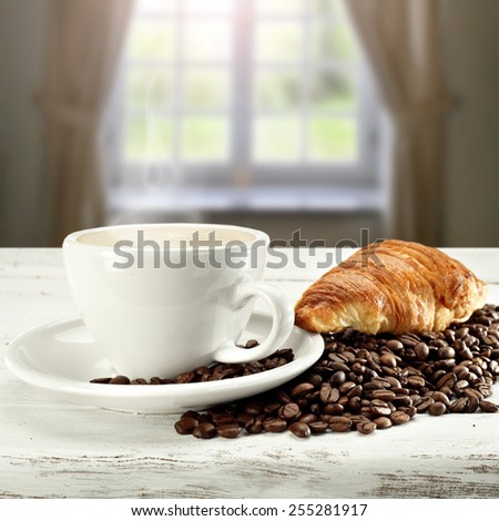 croissant coffee and coffee beans on white table place  - stock photo