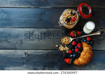 Croissant, fresh berries, yogurt and homemade granola in glass jar for breakfast on dark wooden table. Health and diet concept. Background with space for text. - stock photo