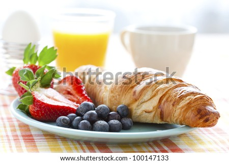 Croissant, fresh strawberries and blueberries, coffee, orange juice and an egg for healthy breakfast - stock photo