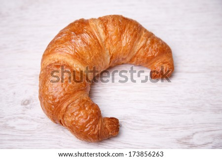 Croissant on a wooden background - stock photo