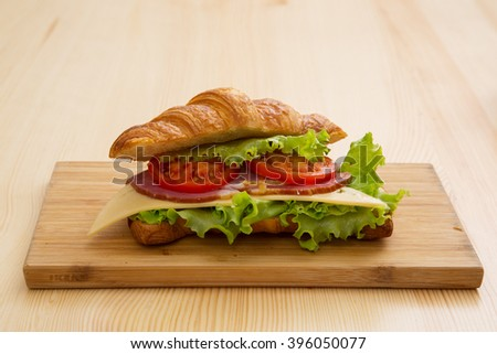Croissant with ham, cheese, lettuce and tomato - stock photo
