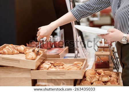 Croissants taste good with jam. Close up of female hand taking croissant to her plate - stock photo