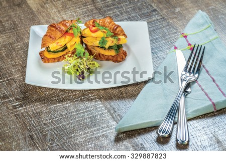Croissants with a fried egg, pesto and roasted zucchini and bell pepper. - stock photo