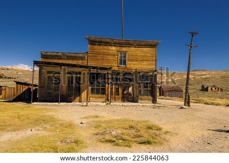 Crooked abandoned building of old western saloon and shop. Ruined business in Bodie Ghost Town - stock photo