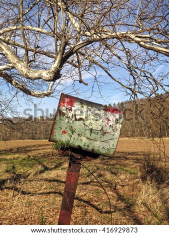 Crooked old, rusty mailbox in the middle of nowhere                                - stock photo