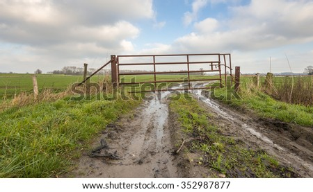 Crooked rusty iron fence at the edge of a meadow. It is autumn and there are puddles of water on the access path. - stock photo