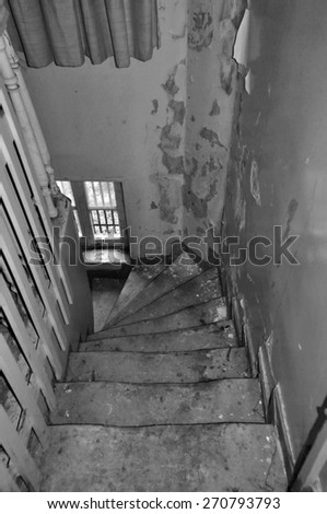Crooked wooden staircase and peeling paint wall in abandoned house. Black and white. - stock photo