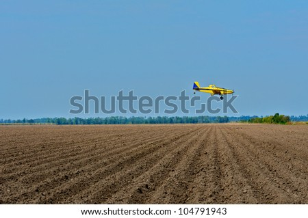 Crop duster approaching fields. - stock photo
