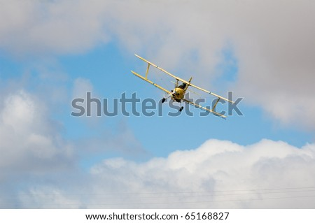crop duster diving in to spray insecticide on crops in central California - stock photo